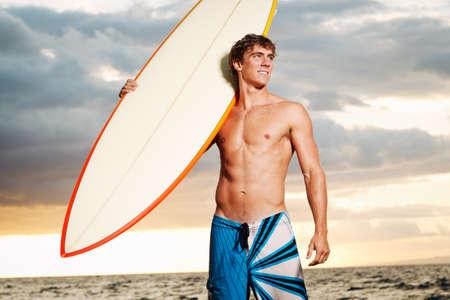 ni�o sin camisa: surfista profesional la celebraci�n de una tabla de surf