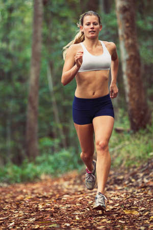 runner girl: woman running outdoors in forest