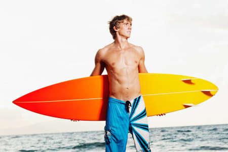 hombres sin camisa: Profesional Surfer sosteniendo una tabla de surf