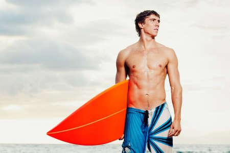 niño sin camisa: Profesional Surfer sosteniendo una tabla de surf