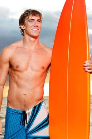 ni�o sin camisa: Profesional Surfer sosteniendo una tabla de surf