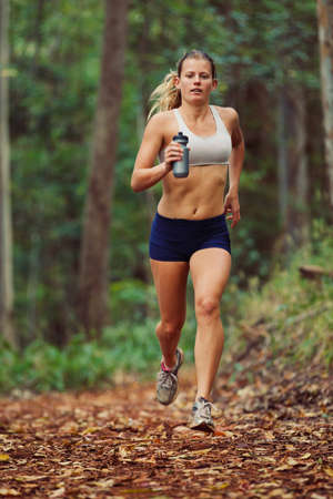 jogger: Woman Running Outdoors in Forest Stock Photo