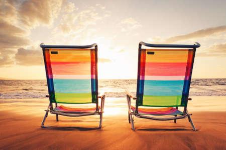 strandstoel: Hawaiian Vacation Sunset Concept, twee strandstoelen bij Zonsondergang Stockfoto