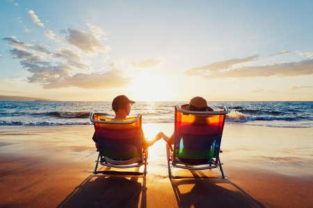 luna de miel: Pareja romántica feliz disfrutando Hermoso Atardecer en la playa Foto de archivo