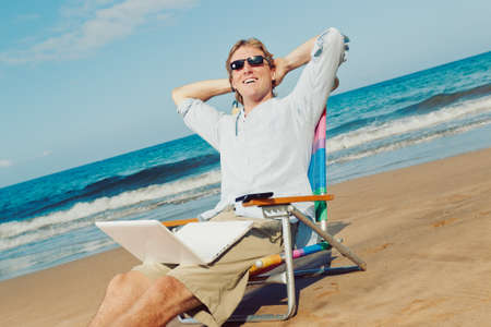 Young Attractive Man Relaxing at the Beach with Laptop Computer photo