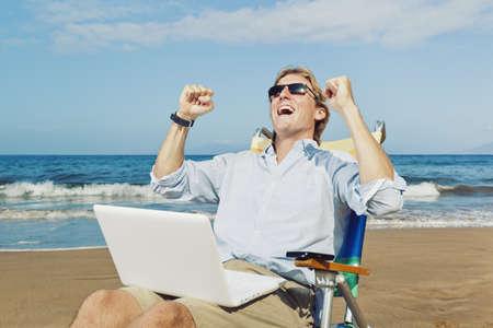 Jonge Aantrekkelijke Man viert succes, werken op de computer op het strand