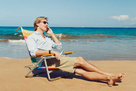 Business man calling by cell phone on the beach in Hawaii Stock Photo - 12952707