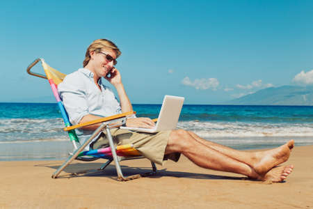 corporate travel: Business man calling by cell phone and working on computer at the beach in Hawaii