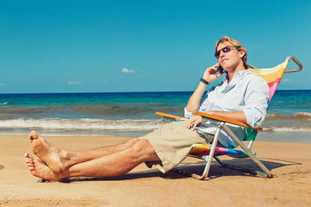 holiday stress: Business man calling by cell phone on the beach in Hawaii