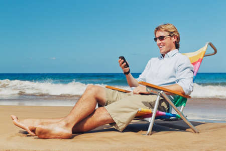 Zakelijk man belt via de mobiele telefoon op het strand in Hawaii