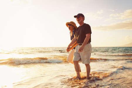 年配のカップル、ビーチで夕日を楽しむ