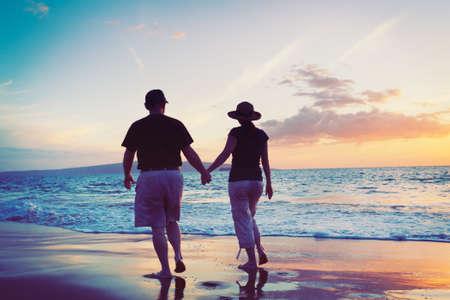 happy retirement: Senior Couple Enjoying Sunset at the Beach
