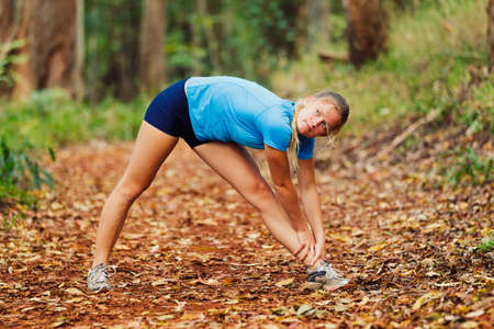 Young Woman Stretching after a Run in the Forest photo