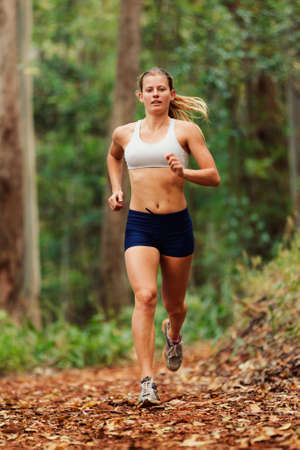 sprinting: Young Woman Running on Trail