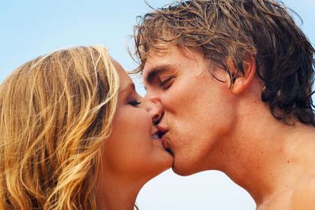 Attractive Young Couple Kissing on Tropical Beach photo