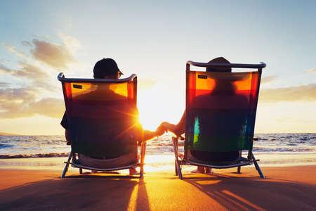 浜の美しい夕日を楽しんで幸せなロマンチックなカップル