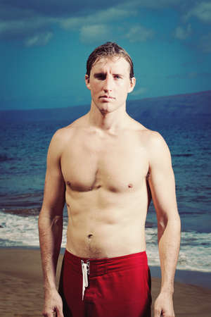 Dramatic Portrait of Handsome Young Fit Man at the Beach Stock Photo