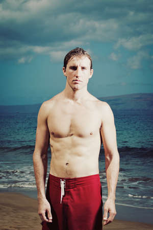 Dramatic Portrait of Handsome Young Fit Man at the Beach photo
