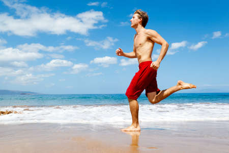 El hombre en buena forma física corriendo en la playa Foto de archivo