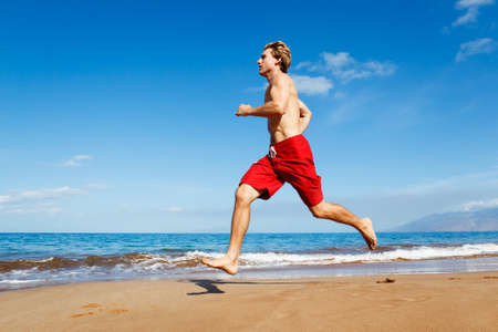 Physically fit man running on Beach Stock Photo - 13299658