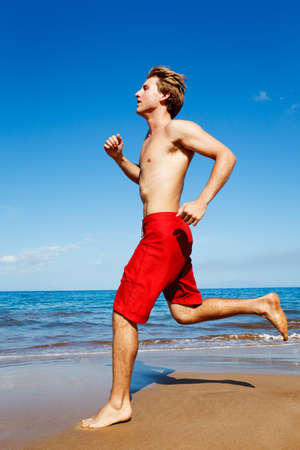 Physically fit man running on Beach Stock Photo - 13299623