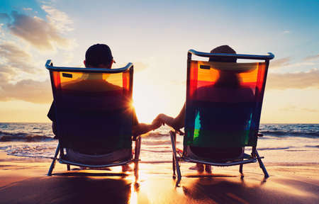 a year older: senior couple of old man and woman sitting on the beach watching sunset