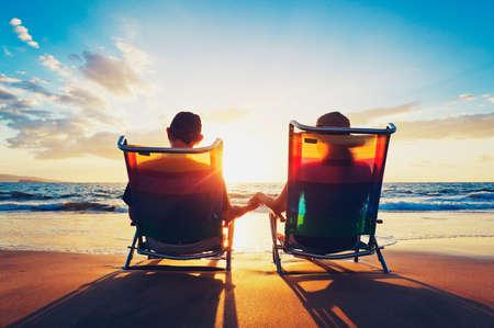 puesta de sol: matrimonios de edad del hombre de edad y una mujer sentados en la playa mirando puesta de sol Foto de archivo
