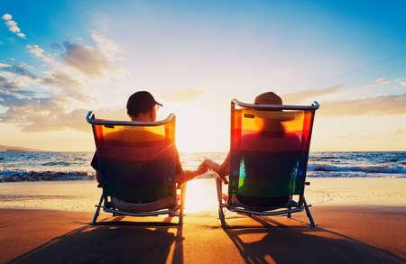 늙은 남자와 여자 석양을보고 해변에 앉아 수석 몇