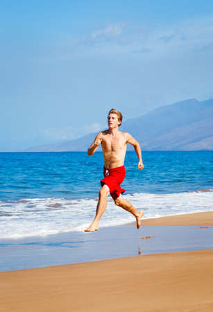 Physically fit man running on Beach in Hawaii Stock Photo - 13406352