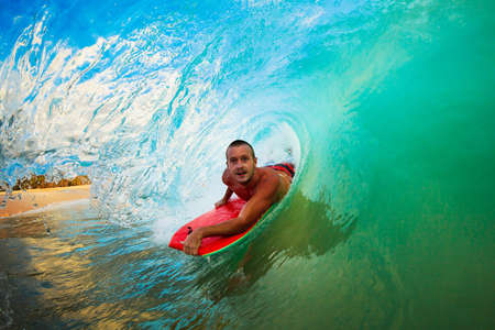 watersports: Body Boarder on Large Wave Surfing in the Tube Getting Barreled