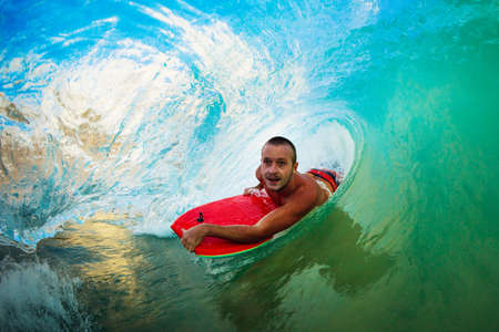 northshore: Body Boarder on Large Wave Surfing in the Tube Getting Barreled