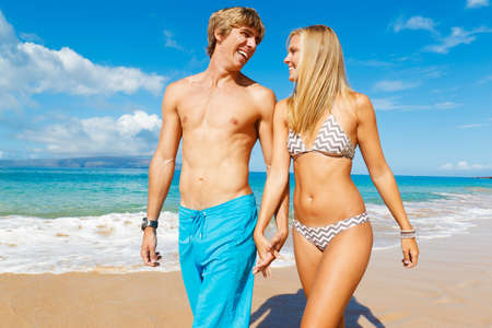 Attractive Couple Walking on Beautiful Beach photo