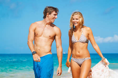 Attractive Couple Walking on Beautiful Beach photo
