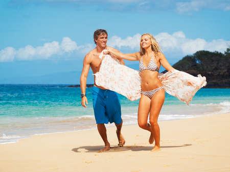 jovenes enamorados: Atractiva Pareja camina en la playa Hermosa Foto de archivo