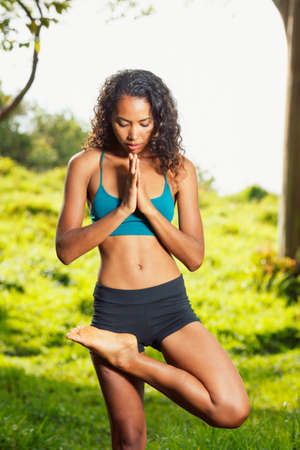 Beautiful Woman Practicing Yoga Outside in Nature photo