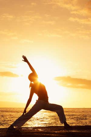 yoga beach: Silhouette of a Beautiful Yoga Woman at Sunset