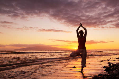 Silhouette of a Beautiful Yoga Woman at Sunset photo