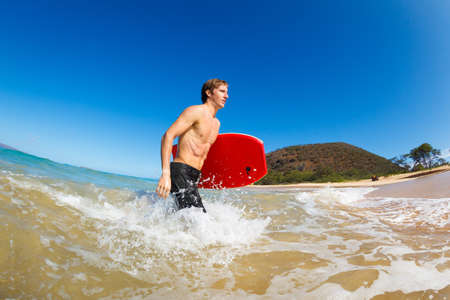 Young Man with Boogie Board at the Beach photo