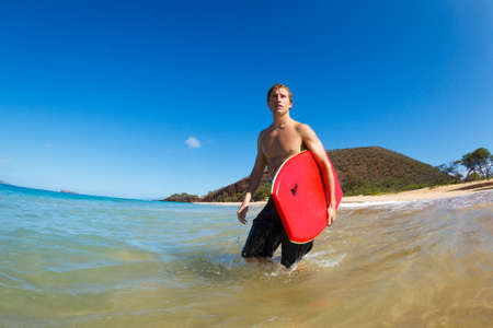 watersports: Young Man with Boogie Board at the Beach