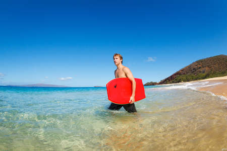 northshore: Young Man with Boogie Board at the Beach