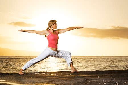 beach yoga: Silhouette of a beautiful Yoga woman in the morning