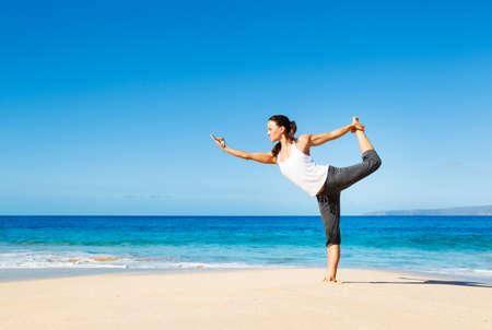 魅力的な女性は、ビーチでのヨガの練習
