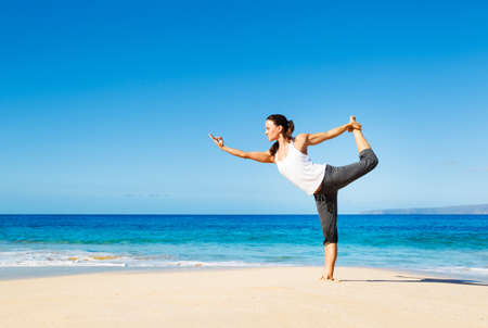 attractive woman practicing yoga by the beach photo