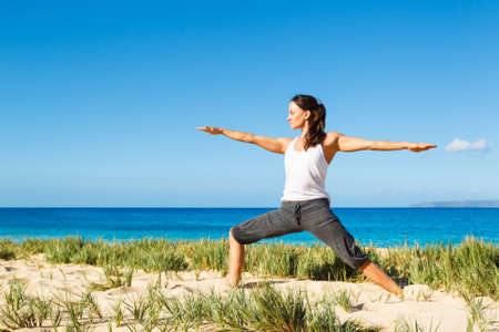 attractive woman practicing yoga by the beach Stock Photo