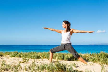 attraktive Frau praktizieren Yoga am Strand Standard-Bild