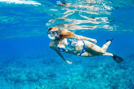 snorkeling: Beautiful Woman Snorkeling in Tropical Ocean Stock Photo