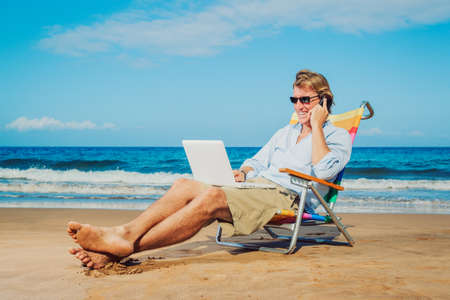 business traveler: Young Business Man Working Remotely on Tropical Beach