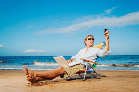 laptop outside: Young Business Man Working Remotely on Tropical Beach