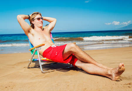 Young Handsome Man Relaxing on Tropical Beach photo