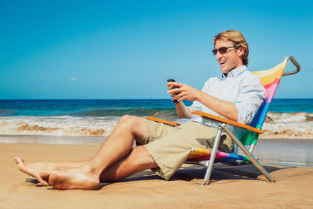 Young Business Man Working Remotely on Tropical Beach photo